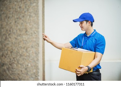 Delivery man with box near house of customer, outdoors