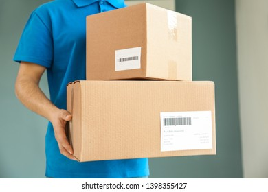 Delivery man with boxes indoors