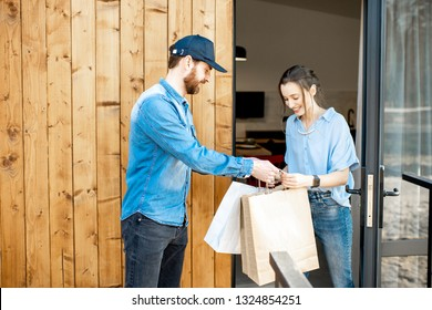 Delivery man bringing some goods packaged in paper bags for a young woman client to home. Buying clothes online and delivery concept