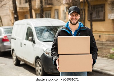 Delivery man with cap and cardboard in hands