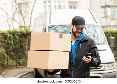 Delivery man with cap and cardboard in hands, searching the adress on the mobile phone