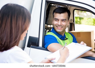 Delivery man in the car delivering parcel to a woman and giving her document to sign