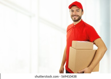 delivery man with cardboard boxes standing in office. copy space