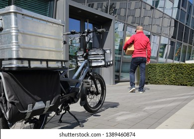 Delivery man with cargo ebike and box in front of an office building entrance.