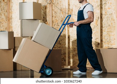 Delivery man carrying boxes on hand truck