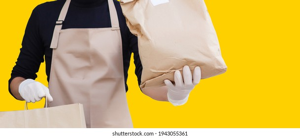 delivery man carrying paper bag with food products isolated over yellow background