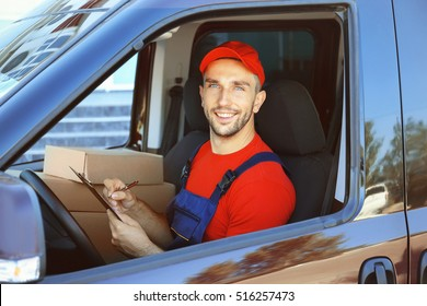 Delivery man checking list in car with parcels