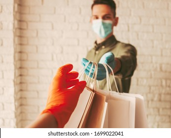 Delivery man courier in protective face mask and medical gloves giving paper bags to customer. Girl receiving paper packages. Safe online delivery from supermarket to home door. COVID-19 coronavirus