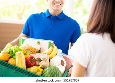 Delivery man delivering food to a woman at home - online grocery shopping service concept