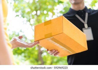 Delivery man delivering package to customer, close up at hand and box