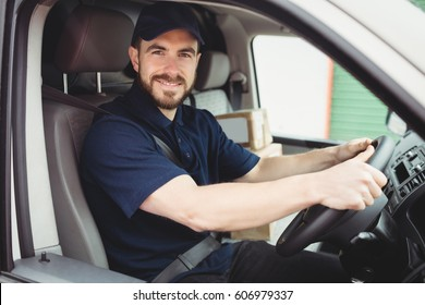 Delivery man driving his van while smiling at camera