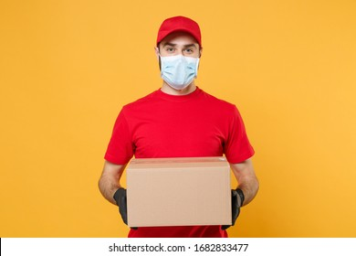 Delivery man employee in red cap blank t-shirt uniform face mask gloves hold empty cardboard box isolated on yellow background studio Service quarantine pandemic coronavirus virus 2019-ncov concept