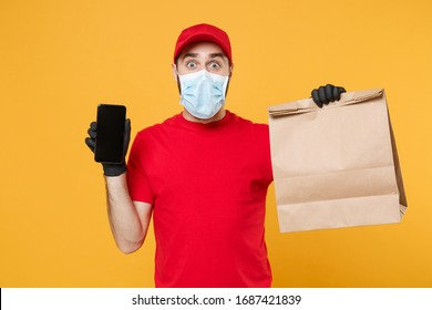 Delivery man employee in red cap blank t shirt uniform mask glove hold craft paper packet cellphone isolated on yellow background studio Service quarantine pandemic coronavirus virus 2019-ncov concept