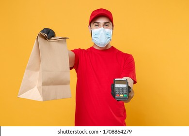 Delivery man employee in red cap blank t-shirt uniform mask glove hold craft paper packet terminal isolated on yellow background studio Service quarantine pandemic coronavirus virus 2019-ncov concept