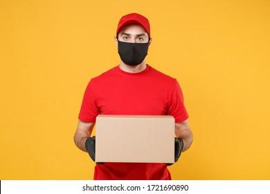 Delivery man employee in red cap blank tshirt uniform face mask glove hold empty cardboard box isolated on yellow background studio Service quarantine pandemic coronavirus flu virus 2019-ncov concept