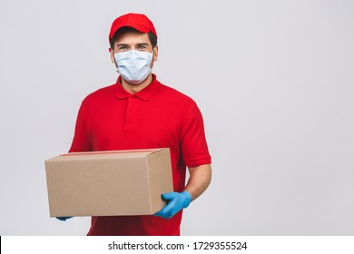 Delivery man employee in red cap blank t-shirt uniform face mask gloves hold empty cardboard box isolated on white background. Service quarantine pandemic coronavirus virus 2019-ncov concept.