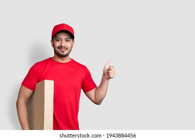 Delivery man employee in red cap blank t-shirt thumbsup uniform