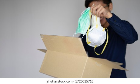 Delivery man employee wearing face mask gloves holding package paper box and opening. In the box store alcohal gel, mask, N95. Service quarantine pandemic coronavirus virus 2019-ncov concept