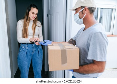 Delivery man with face mask delivering package to woman