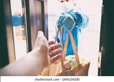 Der Lieferer gibt die Tasche vom Lebensmittelgeschäft an die Frau zu ihr Zuhause.
