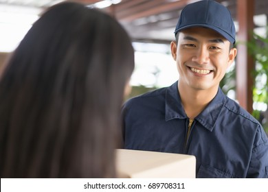 Delivery man giving a cardboard box to young woman while standing in front of the house. Fast and reliable service.