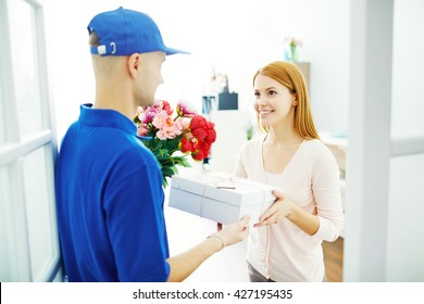 Delivery man giving flowers and present to pretty woman at home
