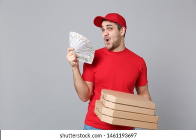 Delivery man giving hold food order pizza boxes isolated on grey background. Professional male pizzaman employee in red t-shirt print working as courier dealer. Service concept. Mock up copy space