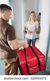 Delivery Man Giving A Large Red Bag To Happy Young Woman