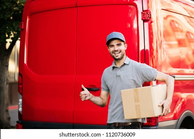 delivery man in grey shirt with cap standing with his cardboard box at the back of his car, ready to give the package to the client, outside on the street, showing confidence and ok sign