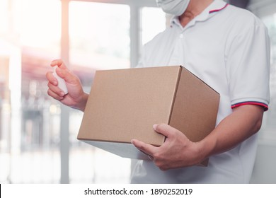 Delivery man hand hold cardboard box delivery Parcel post and  alcohol spray Prevent infection from postage  and protective mask in  home delivery