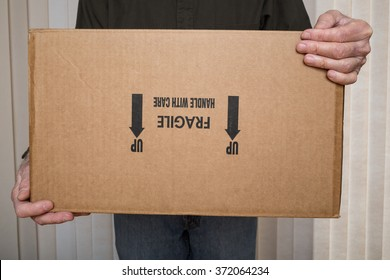 "Delivery man holding a""fragile, handle with care"" package upside down."