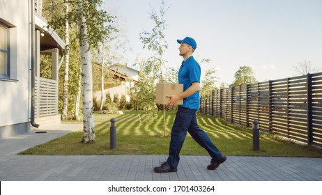 Delivery Man Holding Card Board Package Enters Through the Gates and Walks to the House and Knocks. Delivering Postal Parcel. In the Background Beautiful Suburban Neighbourhood. Side View