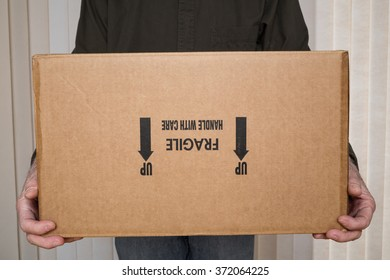 "Delivery man holding cardboard box marked ""fragile, handle with care"" upside down."