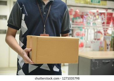 Delivery man holding cardboard boxes in office