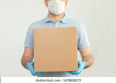 Delivery man holding cardboard boxes in medical rubber gloves and mask. copy space. Fast and free Delivery transport . Online shopping and Express delivery . Quarantine