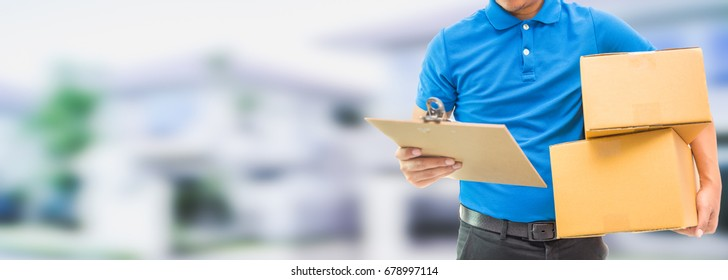 Delivery man holding cardboard boxes / copy space