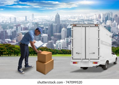 Delivery man holding clipboard for checklist and writing at parcel boxes with delivery van in the city. logistics and shipping concept.