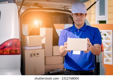 Delivery man holding package in front of cargo van delivering package.