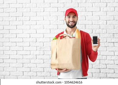 Delivery man holding paper bag with food and phone on brick wall background