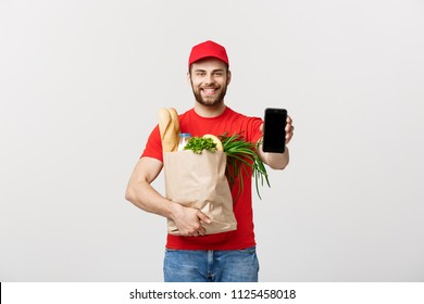 Delivery man holding paper bag with food and showing blank phone screen on white background