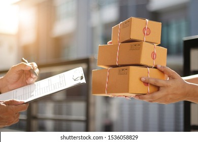 Delivery man holding parcel boxes while a man is signing documents in morning background