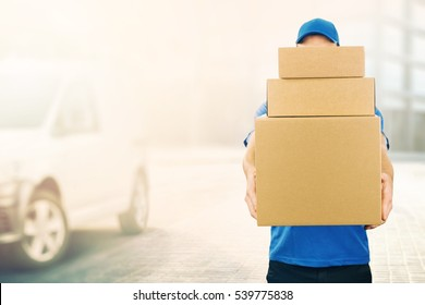 delivery man holding pile of cardboard boxes in front. copy space