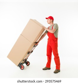 delivery man holding push cart loaded with cardboard boxes, on white background