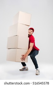 Delivery man lifts the boxes. so hard. isolated gray background