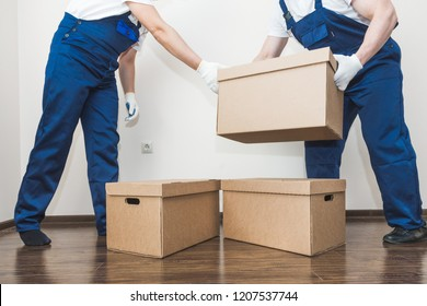 Delivery man loading cardboard boxes for moving to an apartment. professional worker of transportation, male loaders in overalls