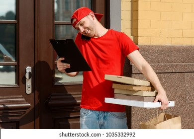 Delivery man near customer's house, checking the receipt and holding several pizza boxes. Part-time job for a student.