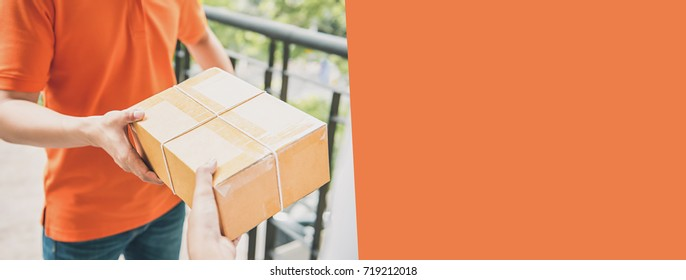 Delivery man in orange uniform handing a parcel box over to a customer, courier service concept - horizontal web banner background with copy space on the right