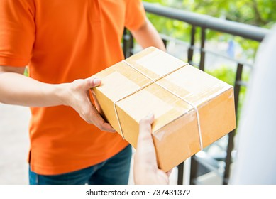 Delivery man in orange uniform handing a parcel box over to a customer  - courier service concept