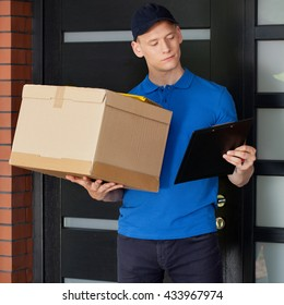 Delivery man with parcel and clipboard waiting at front door