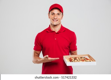 Delivery man with pizza in studio. looking at camera. isolated gray background